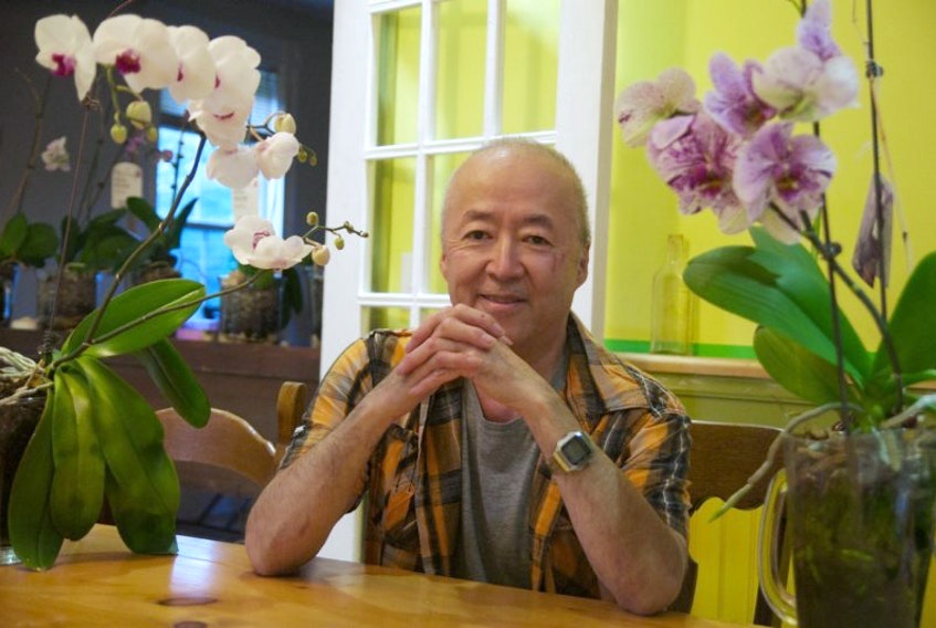 Dr. Ronald Matsusaki sits in his home with his orchids, many of which he nursed back to health after buying them half price. The waiting area in his clinic was full of his orchids and was affectionately nicknamed the 'Orchid Cafe.'