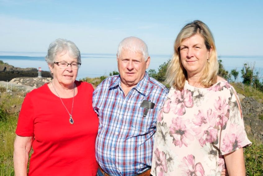 Marilyn and Lewis Walker stand with Elizabeth Lore in front of Centreville Harbour in Trout Cove, on the Bay of Fundy, one of the two bays surrounding the Digby Neck.